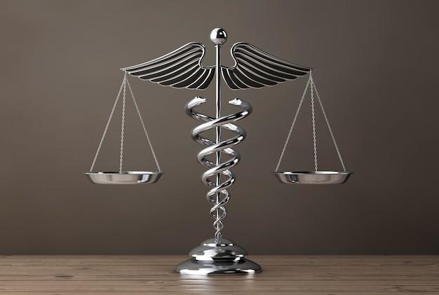 木製のテーブルの上の鱗としての銀の医療カドゥケウスのシンボル。 3dレンダリング