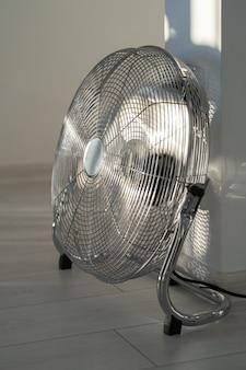 Серебряный металлический вентилятор на деревянном полу дома