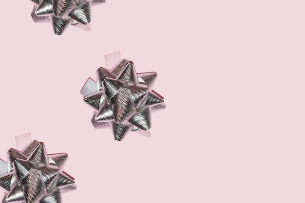 Серебряная металлическая звездная лента на пастельно-розовом фоне для рождественского фона