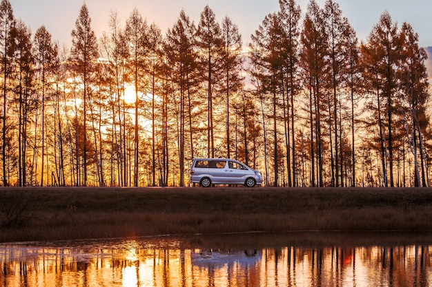 Серебряный минивэн на фореат-роуд у озера на закате