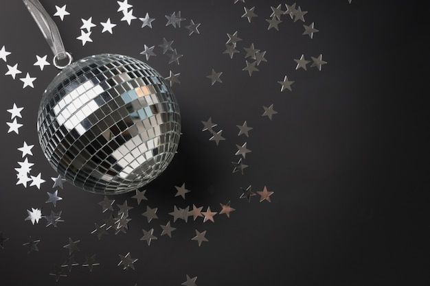 Silver mirror disco ball glitter with stars on black background. festive holiday concept.