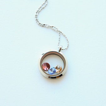 Серебряное колье для нее сияет на белом фоне. роскошные серебряные ювелирные цепочки со стеклом и кристаллами. маленький красивый подарок из драгоценного металла для женщины. роскошный серебряный ювелирный магазин блестящих браслетов