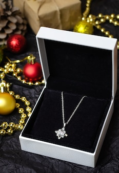 Silver necklace in gift box on black.