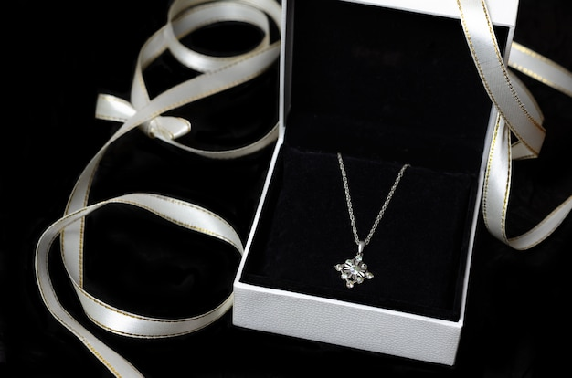 Silver necklace in gift box on black