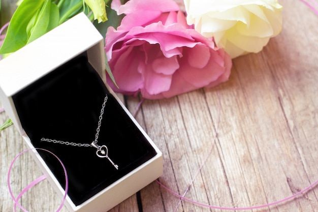 Silver necklace in gift box on wooden