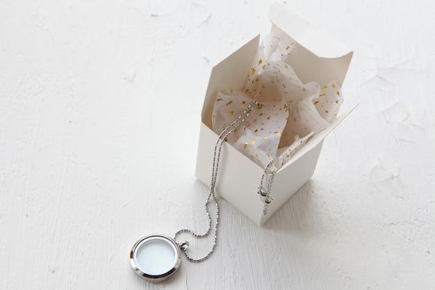 白い背景の上の銀のネックレス。ギフトボックスの近くにガラスが付いた豪華なシルバージュエリー。彼女へのささやかなプレゼント。テキスト用のコピースペースを備えた美しい貴重な女性のジュエリー。