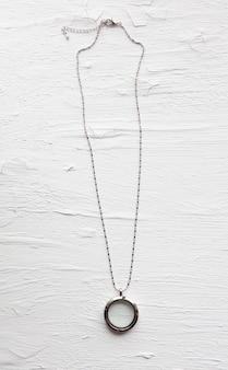 白い背景の上の銀のネックレス。ガラスの高級シルバージュエリー。彼女へのささやかなプレゼント。コピースペースのある美しい貴重な女性のジュエリー