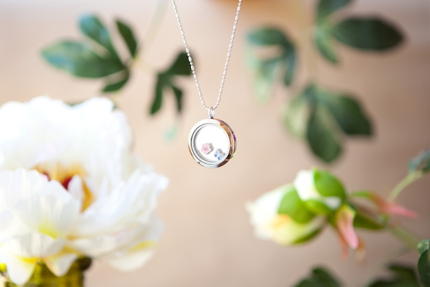 Silver necklace on peonies flower background luxury jewelry chains with glass precious metal