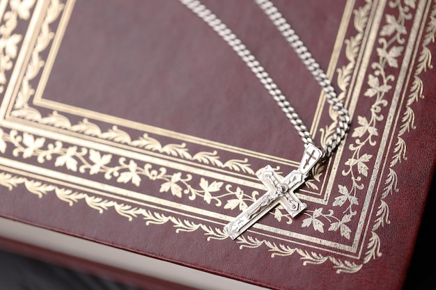 Silver necklace with crucifix cross on christian holy bible book on black wooden table.