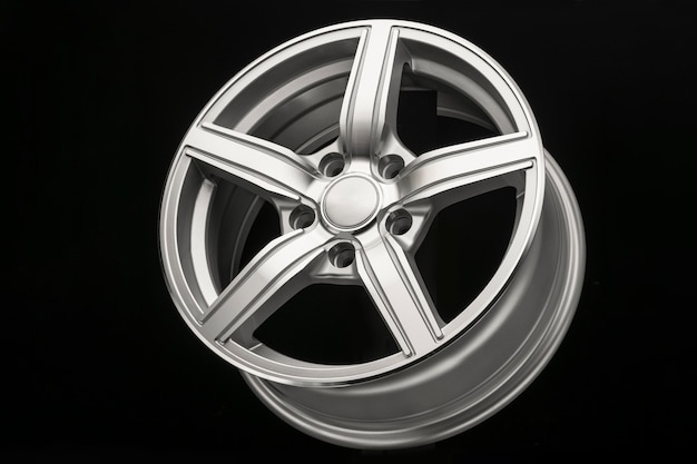 Silver new alloy wheel for car, side view close-up, polished.