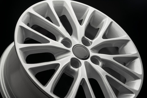 Silver new alloy wheel for car, side view close-up.