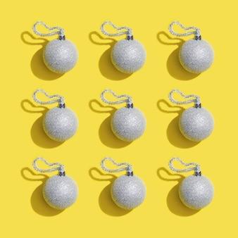 Серебряные новогодние шары, праздничная игрушка на желтой рождественской открытке. минимальный стиль трендовый цвет 2021 года