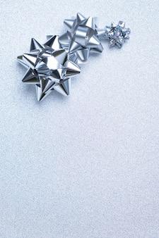 銀の背景に銀のパッケージの弓。