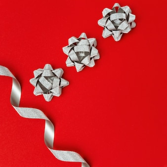 Silver paper ribbon tie on red background with copy space, christmas gift packaging decoration.