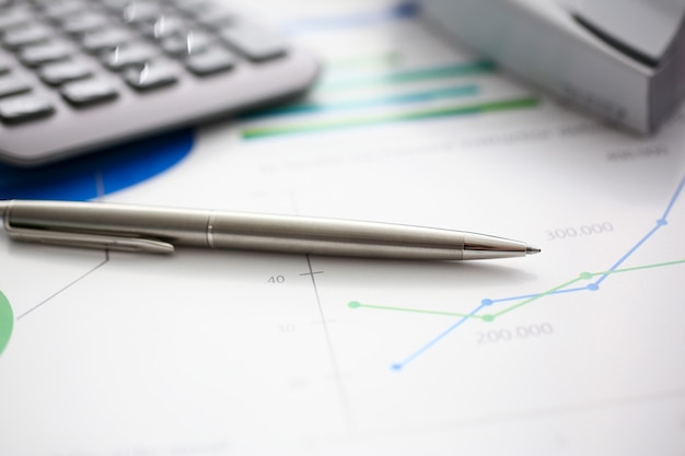 Серебряная ручка и калькулятор на рабочем месте готовы к использованию