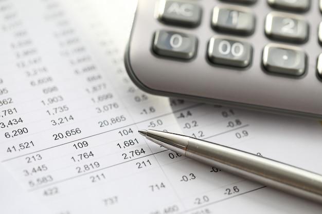 Серебряная ручка лежит на отчете с номерами, калькулятором. предварительный анализ целевой аудитории. инвестор инвестирует в этот инвестиционный проект. выбор продукта или нового бизнеса для выхода на рынок