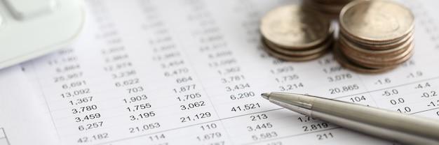 Серебряная ручка лежала над финансовой статистики бумаги с набором чисел крупным планом