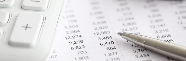 Серебряная ручка отчет с номерами рядом с калькулятором. спектр финансовых инструментов для торговли на бирже. анализ финансовых данных. маркетинговая тактика и ведение бизнеса
