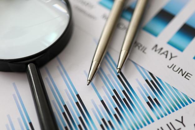 Серебряные ручки лежат на красочных статистических документах с крупным планом увеличительного стекла