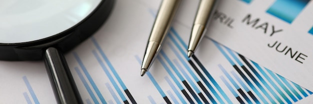 Silver pens lying at colorful statistics documents with magnifying glass