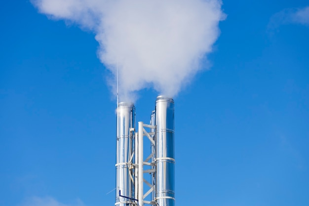 青い空に煙が出る銀のパイプ。高品質の写真