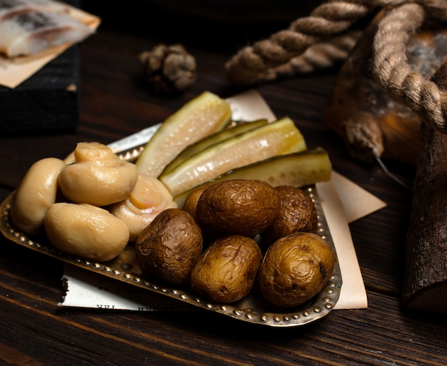Silver plate of pickled mushrooms, cucumbers and baked potatoes
