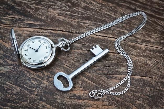 Серебряные карманные часы и ключ на деревянной текстуры.