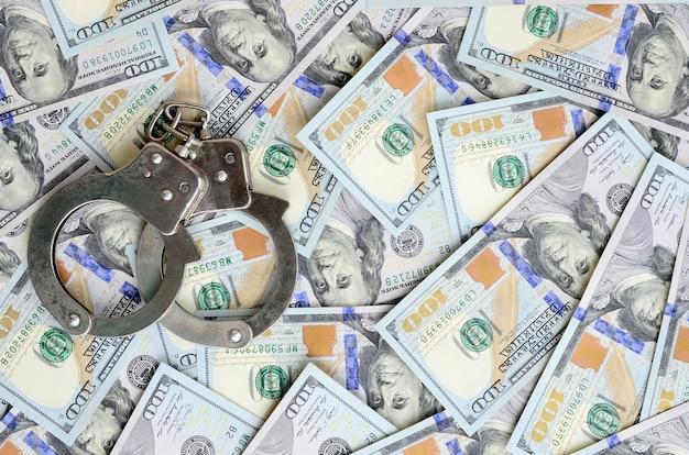 Silver police handcuffs lies on a many dollar bills