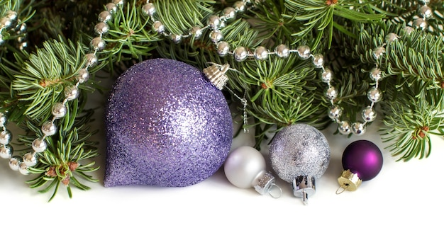 Silver and purple christmas ornaments border on white close up