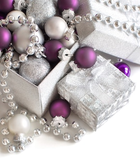 Silver and purple christmas ornaments close up isolated on white