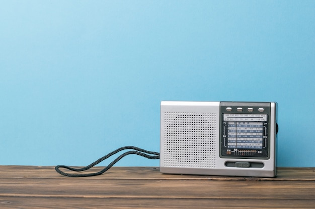 青い背景の上の木製のテーブルの上の銀のレトロなラジオ。