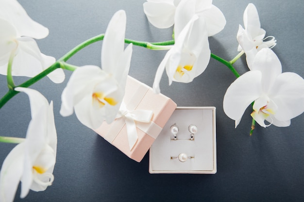 Silver ring and earrings with pearls in gift box with white orchid flower. present for holiday. fashion accessories