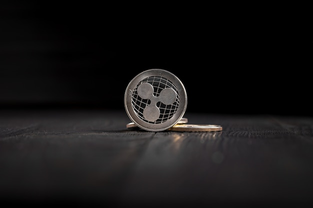 Silver ripple coins on black wood