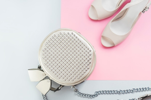 Silver round bag on the chain with metal cleat and stylish female milk color wedding heel shoes on blue pink background.