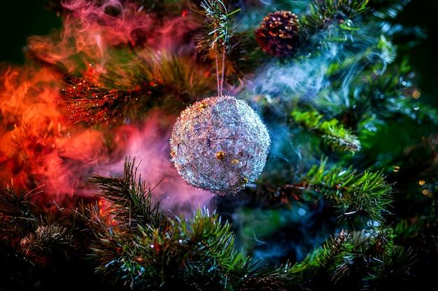 Серебряный блестящий новогодний шар в цветном пурпурно-красном дыму на елке