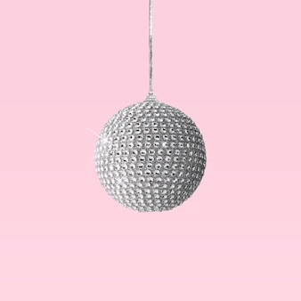 Silver shiny christmas bauble decoration on pink
