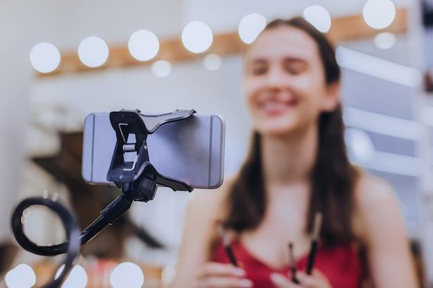 シルバーのスマートフォン。彼女の銀色のスマートフォンでビデオを作っている間、笑顔の魅力的なブロガーは素晴らしい気分です