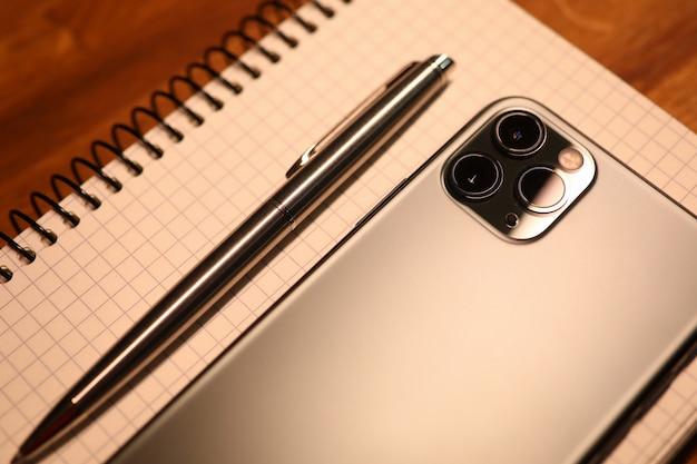 銀のスマートフォンとペンでノートブックはオフィスのクローズアップの木製テーブルにあります。