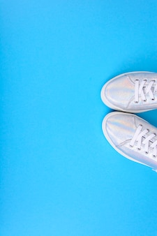 Серебряные кроссовки на синем фоне с местом для текста. студийное фото