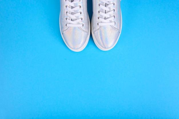 Серебряные кроссовки на синей поверхности с местом для текста