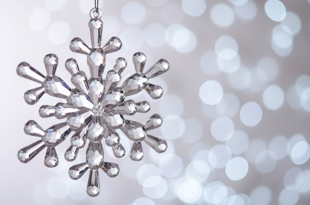 Silver snowflake hangs on a christmas tree branch
