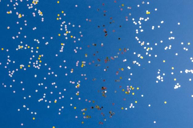 ブルーのトレンディな背景にシルバーが輝きます。プロジェクトのお祝いの背景。フラットレイスタイル。上面図。今年の色。