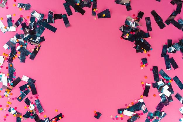 Серебряная блестка мишура на розовом фоне