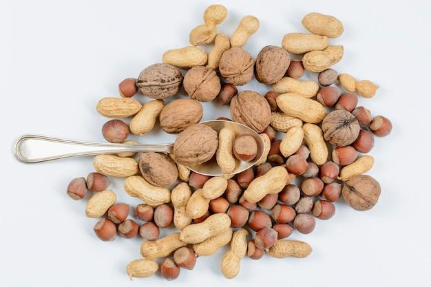Серебряная ложка со смесью орехов на белом фоне. понятие о правильном питании.