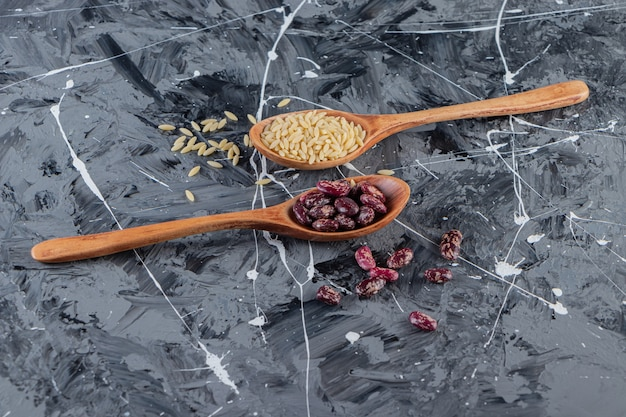 Silver spoons full of long rice and beans on marble background.