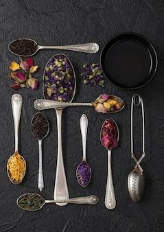 ヴィンテージストレーナー注入器付き鉄カップと黒に様々なお茶と銀のスプーン。上面図