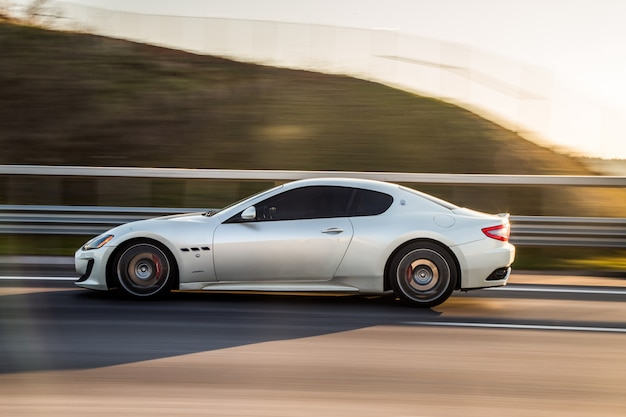 A silver sport coupe driving in the highway.