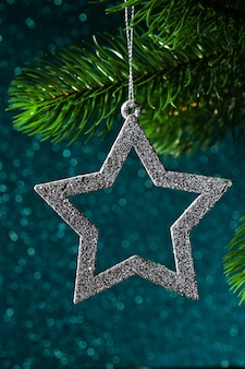 Silver star on a christmas tree branch on a blue shining background from bokeh.