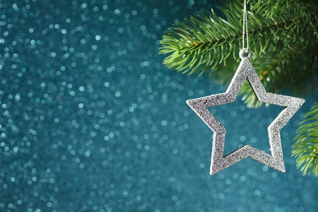Silver star on a christmas tree branch on a blue shining bokeh background, new year decorations.