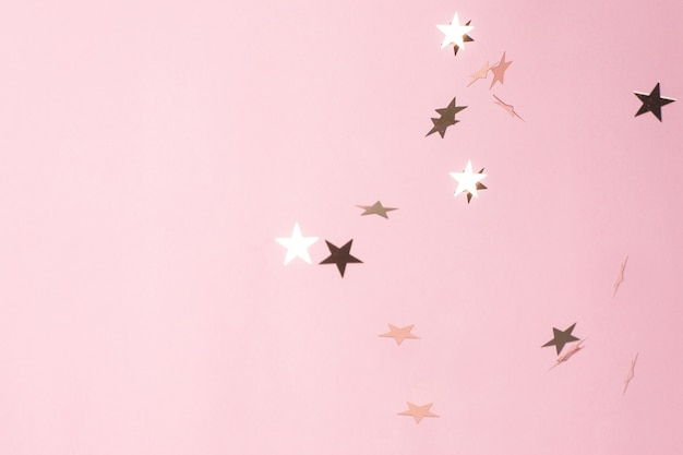 Silver star confetti on pastel pink background.
